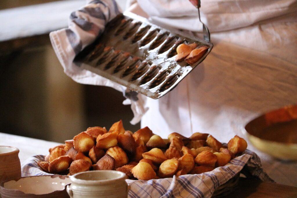 Madeleines chaudes au miel sortant du four, elles sont déposées dans un plats avec d'autres madeleines, gourmandises assurée