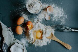 Farine de Sarassin - farine sur plan de travaille avec des oeufs et ustensiles de cuisine